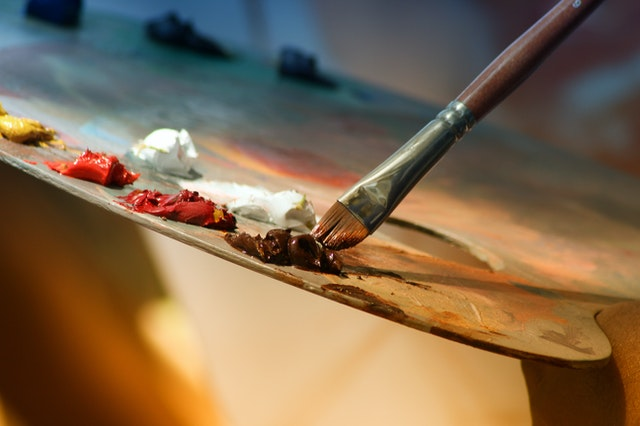Painter's palette with a paintbrush dipping into paint